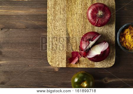 Red bisect onion tomato turmeric on wooden table. Close-up from above.
