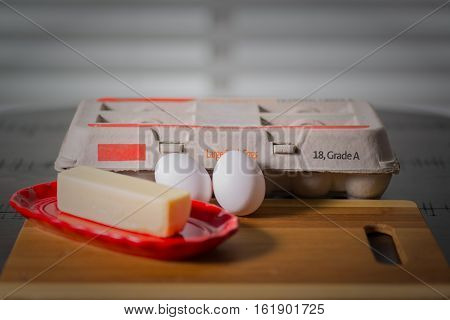 Eggs with real butter, egg carton and butter dish on a round dark wooden table.