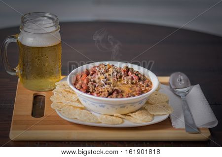 Chilli con carne with paprika tomatoes onion red bean and garlic in a white bowl, with tortilla chips with a cold sweaty beer.
