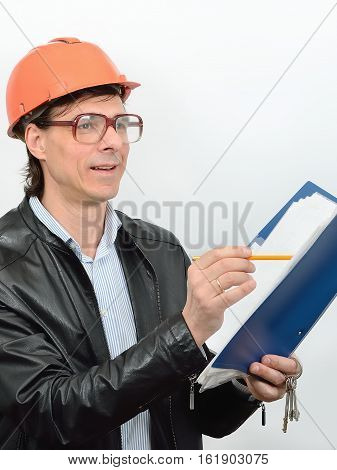 Portrait of male construction worker construction superintendent in glasses protective helmet with a folder of documents and pencil in hand