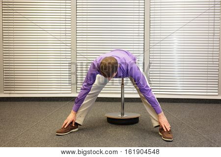 man exercising on stool in office,touching his feet, healthy lifestyle - front