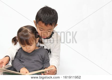 Japanese brother and sister reading a picture book (7 years old boy and 2 years old girl)