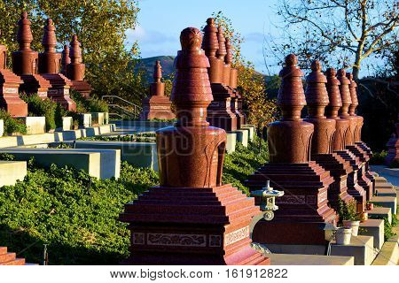 Gravesites at a Buddhist Cemetery with tall headstones surrounded by lush landscaping