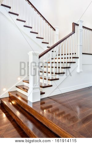 Stairs and glossy wooden floor of beautiful attractive luxury house with white walls