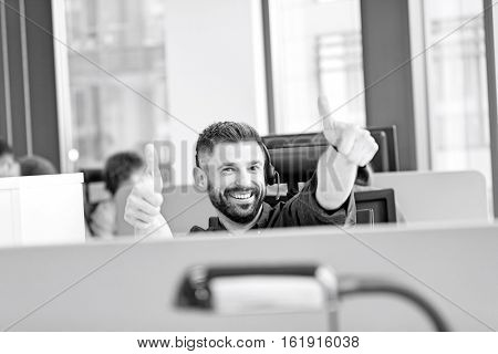 Portrait of happy mid adult businessman wearing headset while gesturing thumbs up in office