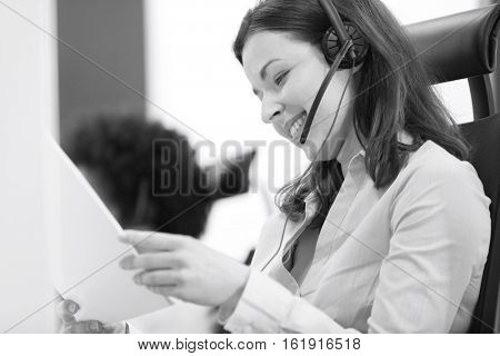 Young businesswoman wearing telephone headset while reading document in office