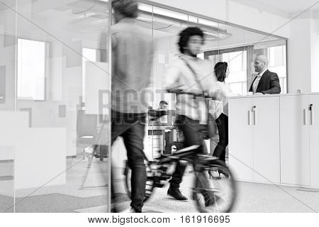 Blurred motion of colleagues with business people discussing in background at office
