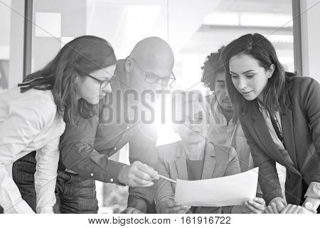 Multi-ethnic business people discussing over document in office