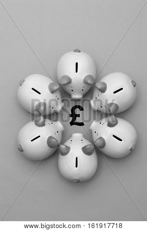 Piggy banks on background surrounding a GBP Symbol