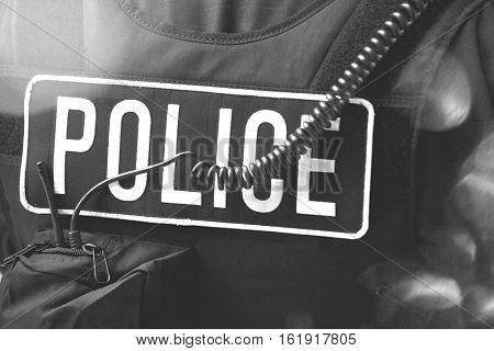 Closeup rear view of policeman's sign and cord on protective jacket