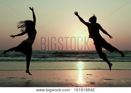 Silhouettes of happy couple jumping on background of sea at sunset