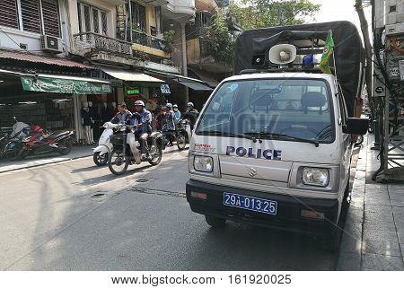 Hanoi, Vietnam - Dec 17, 2016: Vietnamese police security officer truck parking on the side of an old Hanoi quarter street.
