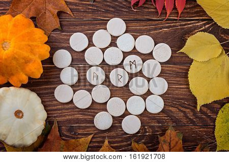 Wooden runes on autumn background. Esoteric tools.