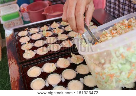 Process of cooking takoyaki on street food in the makets