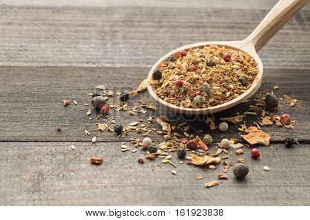 Spices in wooden spoon on table. Culinary background.