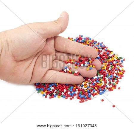 Colorful plastic polymer granules in man hand on white background
