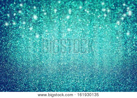 Blue Christmas glitter background with stars textured surface selective focus