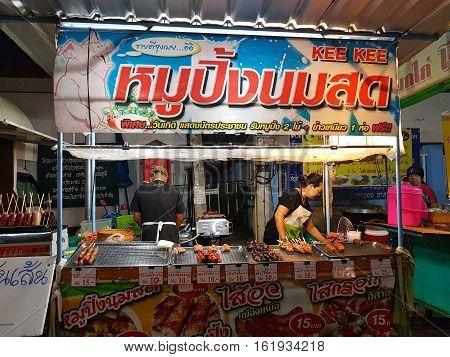 CHAIYAPHUM THAILAND - NOVEMBER 27 : unidentified woman selling grilled pork in bamboo sticks at walking street in night market on November 27 2016 in Chaiyaphum Thailand