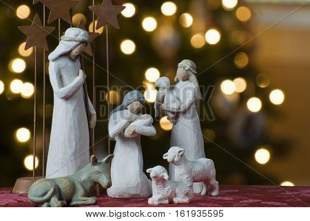 Christmas scene with figurines. Baby Jesus Mary Joseph white statue on light bokeh background.
