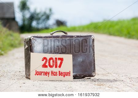 2017 Journey Has Begun. Old traveling suitcase on country road.
