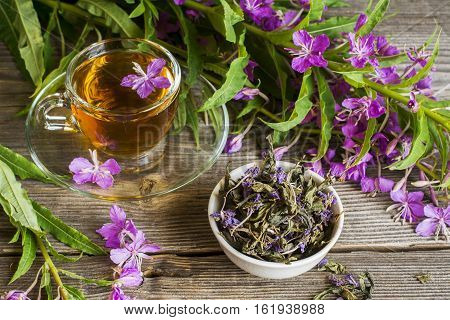 blooming Sally, collected and dried brewing herbal tea useful scattered on the wooden background with flowers and a cup of tea. selective Focus