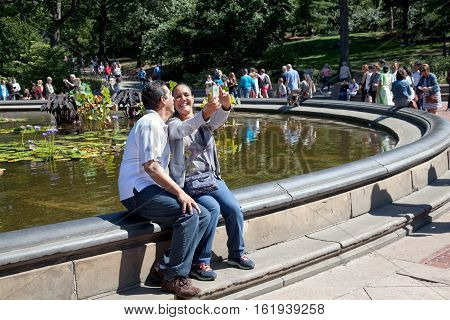 NEW YORK CITYUSA - september 20 2015: Couple in love taking a Selfie with a phone on a pond in Central Park in ManhattanNew York