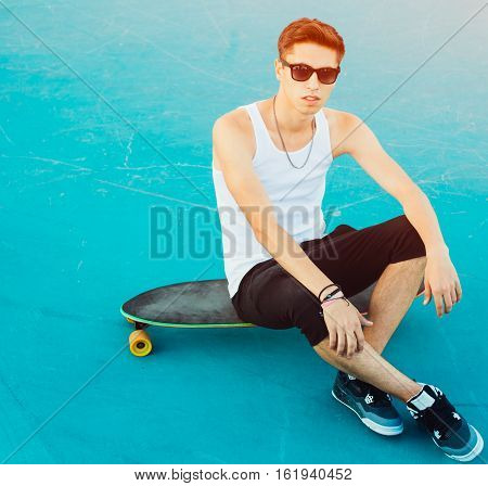 Fashionable young man sitting on a longboard in the ramp for skateboarding in the summer. A skateboarder wearing white shirt, shorts and sneakers. Outdoor.