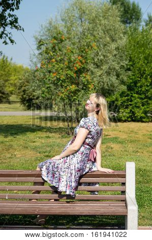 Pregnant woman sitting on wooden bench in park