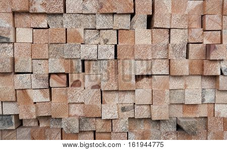 Background of many ends of square section wooden pine sticks.