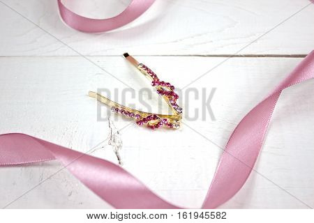 Golden hairpins with pink gemstone and pink ribbon on white wood