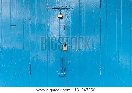 Blue wooden door with the three padlock