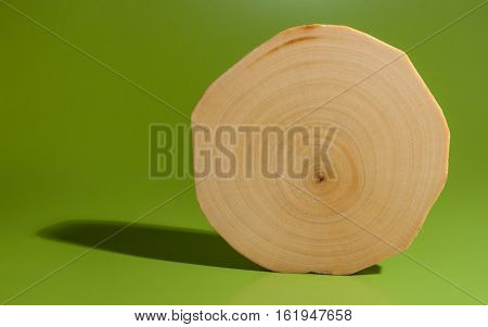 One polished and oiled alder saw cut is standing on green background.