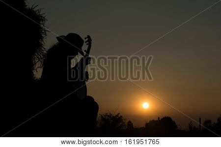 A young man playing the banjo The straw in the field The golden sun warm happily. Beautiful shadows.
