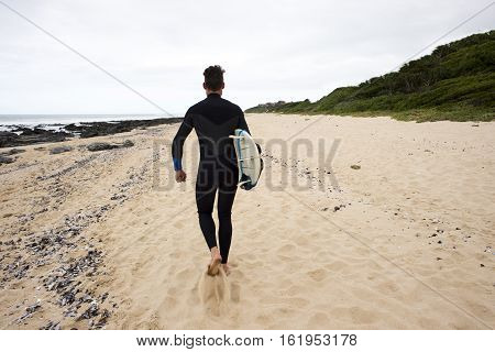 A surfer dude walks along the beach with a surfboard tuck underneath his arm while wearing a wetsuit as seen from behind.