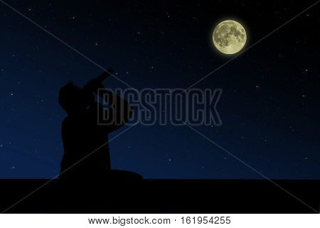 The man sitting on the roof and looks through binoculars at the full moon night.