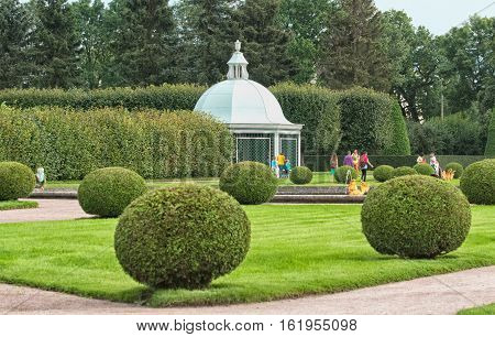 Peterhof, Saint - Petersburg, Russia - August 19, 2016: The Upper Garden. Tourists walk near Mezheumniy (Indefinite) Fountain, The Trellis Pavilion and Berceau.