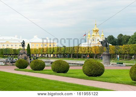 PETERHOF, SAINT - PETERSBURG, RUSSIA - AUGUST 19, 2016: The Upper Garden with Neptune Fountain and Apollo Belvedere Statue. On The background is The Grand Palace and The Curch of Saints Peter and Paul