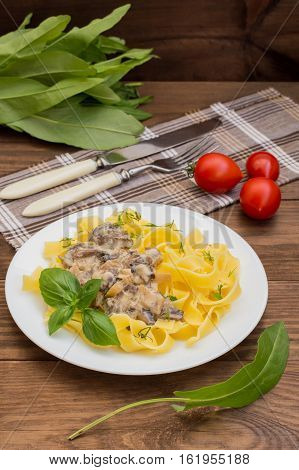 Fettuccine pasta in a creamy sauce with mushrooms on a plate on a wooden table. top view