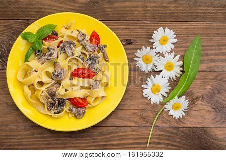 Fettuccine pasta in a creamy sauce with mushrooms on a plate on a wooden table. Horizontal top view