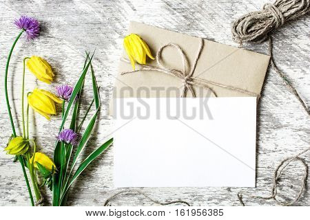 bouquet of wildflowers and blank white greeting card with envelope and rope mockup on brown rustic wood background for creative work design. top view