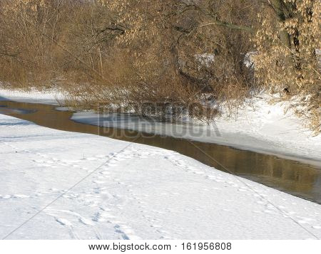 Winter sunny day, small river, snow banks and trees on a far bank
