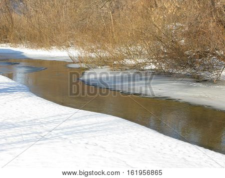 Winter sunny day, narrow small river, snow banks and trees on a far bank