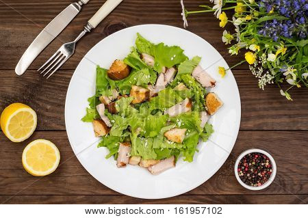 Salad of smoked chicken, croutons, lettuce and parmesan. Wooden rustic background. Top view
