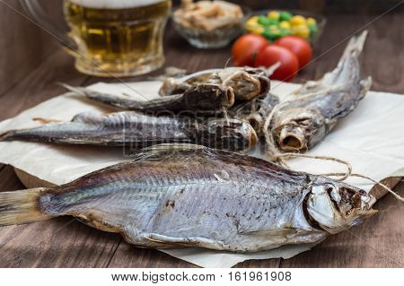 Dried fish, roach with a glass of cold beer on a wooden table. Top view