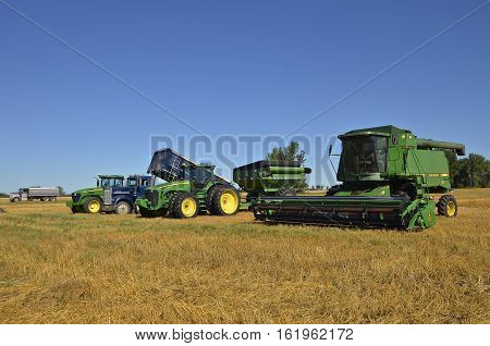BARNESVILLE, MINNESOTA, August 4, 2016 : The combine and harvest equipment tined up in a wheat field are products of John Deere Co, an American corporation that manufactures agricultural, construction, forestry machinery, diesel engines, and drivetrains.