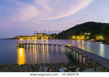 Wooden walking way leading to ocean at twilight, natural landscape background