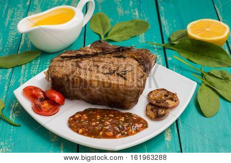 Beef steak medium rare on the grill with barbecue sauce. wood background. Close-up