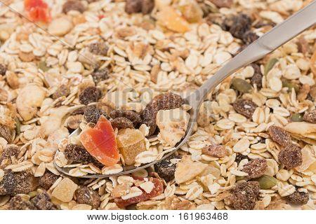 Spoon With Muesli, On Pile Of Muesli Background.