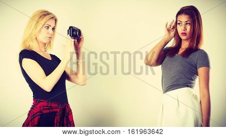 Blonde Girl Photographing Mulatto Woman