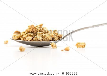 Spoon with granola cereal on white background.